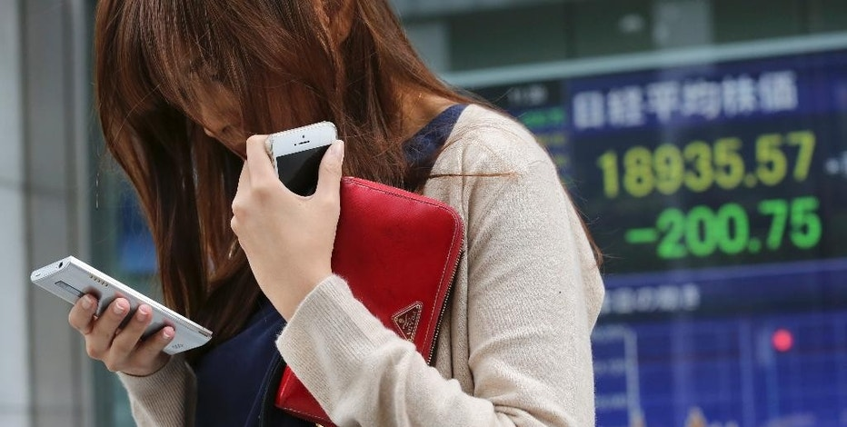 A woman looks at her cell-phone in front of electronic stock board of a securities firm in Tokyo, Monday, Aug. 31, 2015. Asian stocks fell Monday after a U.S. Federal Reserve official suggested a September interest rate hike still was possible and Japanese factory activity weakened (AP Photo/Koji Sasahara)