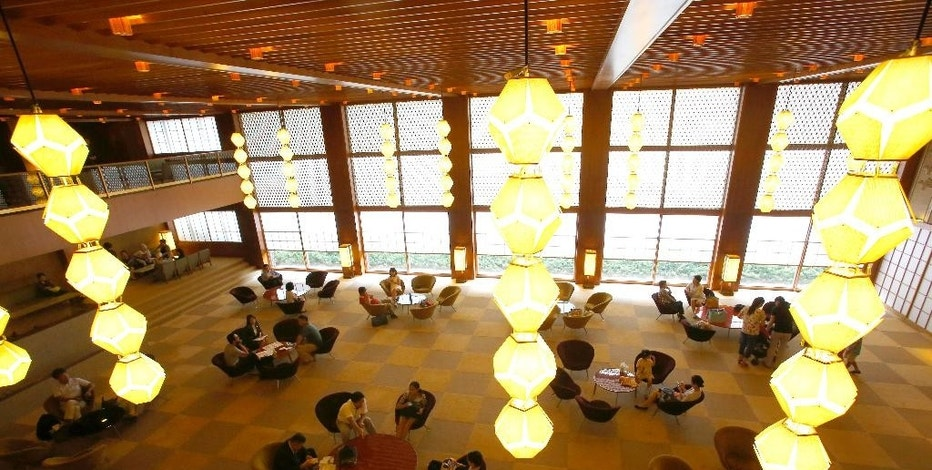 In this photo Thursday, Aug. 20, 2015, visitors relax at the lobby at main lobby of Hotel Okura in Tokyo. The Hotel Okura, a favored Tokyo lodging for U.S. presidents, movie stars and other celebrities, is closing the doors of its iconic, half-century-old main building on Monday, Aug. 31, 2015, to make way for a pair of glass towers ahead of the 2020 Olympics. (AP Photo/Shizuo Kambayashi)