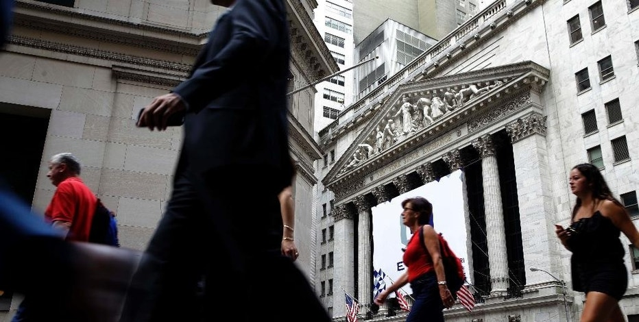 In this Monday, Aug. 24, 2015, photo, pedestrians walk past the New York Stock Exchange. Global stocks mostly fell on Monday, Aug. 31, 2015, after a U.S. Federal Reserve official suggested a September interest rate hike still was possible and weak Japanese factory activity provided more evidence of a sluggish global economy. (AP Photo/Seth Wenig)