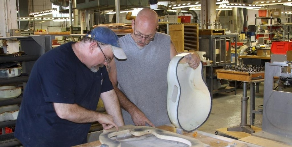 In this Aug. 31, 2015 photo Ovation Guitars plant manager Darren Wallace, left, and Joe Martocchio discuss the manufacture of a guitar at the reopened factory in New Hartford, Conn. The factory that produced Ovation guitars for nearly a half century before closing last year will be making the renown instruments once again, thanks to the efforts of Wallace, who maintained the factory on his own in hopes a new buyer would revive it. (AP Photo/Kathryn Boughton)