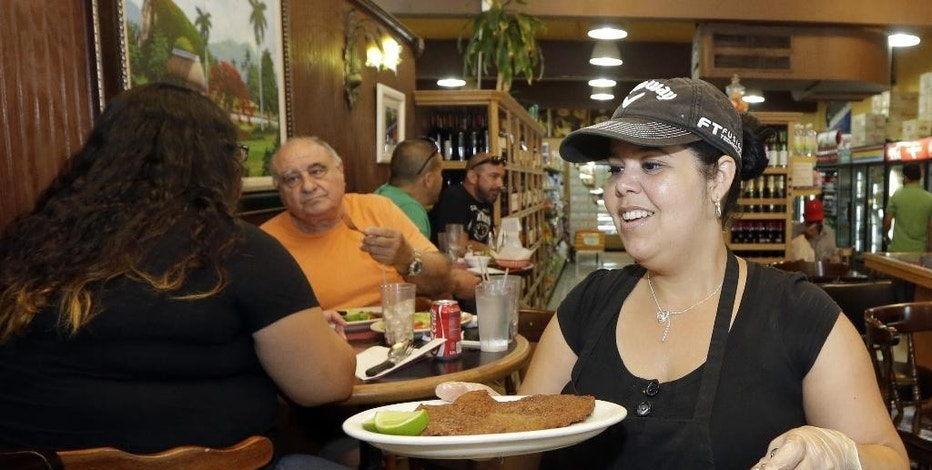 In this photo taken Friday, June 12, 2015, Judith Castro serves a lunch order at a local grocery store in the Little Havana area of Miami. The Institute for Supply Management, a trade group of purchasing managers, issues its index of non-manufacturing activity for August 2015 on Thursday, Sept. 3, 2015. (AP Photo/Alan Diaz)