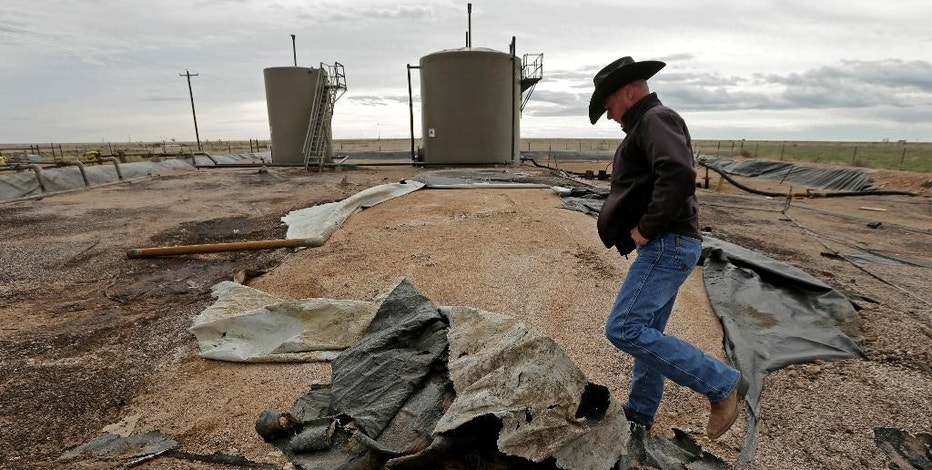 In this April 24, 2015 photo, Justin Johnson looks at a torn lining at a tank and pipeline station adjacent to his ranch near Crossroads, N.M. Trucks bring oilfield wastewater to the station, where it is pumped through pipelines to a disposal well. The lining is intended to prevent wastewater from seeping into the ground in the event of a leak, but it is in poor condition. (AP Photo/Charlie Riedel)
