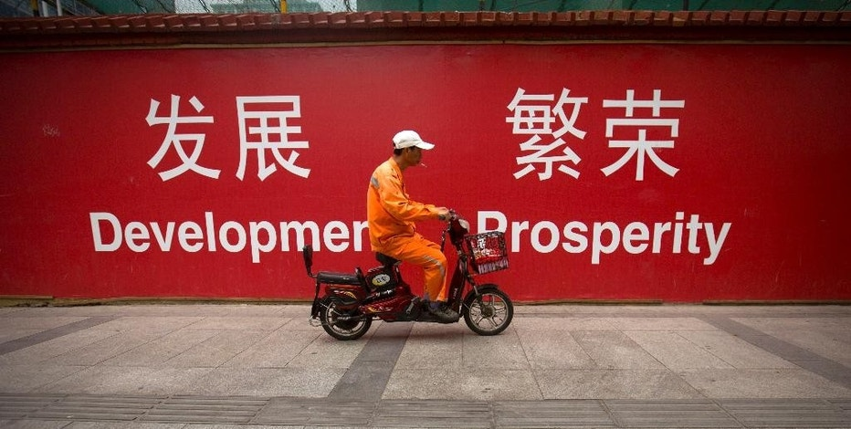 "FILE - In this July 15, 2015 file photo, a maintenance worker rides a scooter past banners reading ""Development"" and ""Prosperity"" in English and Chinese on a street in central Beijing.  The world's second largest economy is decelerating, and the prospect of its slowing growth is rattling financial markets around the world. But China also is shifting, from a dependence on exports and investment in factories, infrastructure and housing to a reliance on consumer spending from the country's emerging middle class. (AP Photo/Mark Schiefelbein, File)"