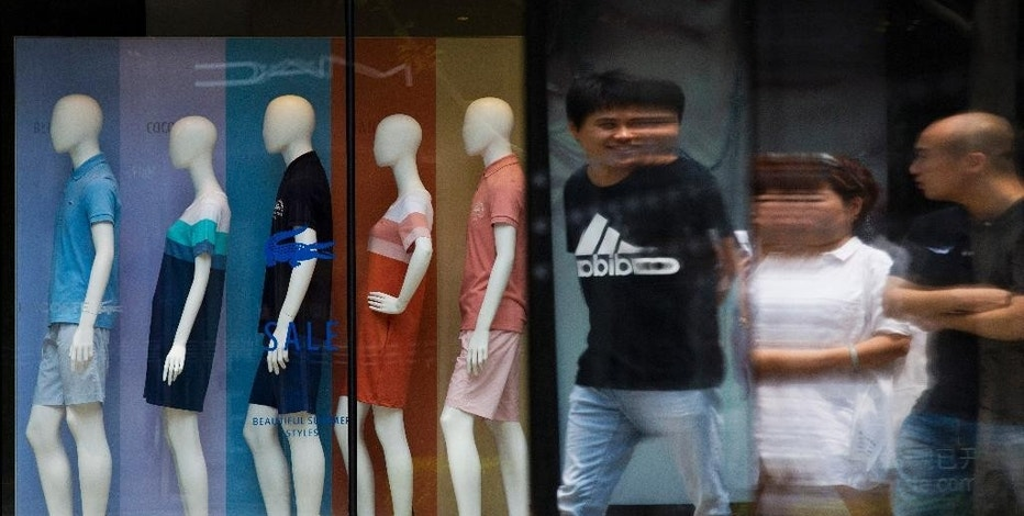 FILE - In this Tuesday, July 14, 2015 photo, people are reflected on a window as they walk past mannequins on display at a boutique in Beijing. The world's second largest economy is decelerating, and the prospect of its slowing growth is rattling financial markets around the world. But China also is shifting _ from a dependence on exports and investment in factories, infrastructure and housing to a reliance on consumer spending from the country's emerging middle class. (AP Photo/Andy Wong, File)