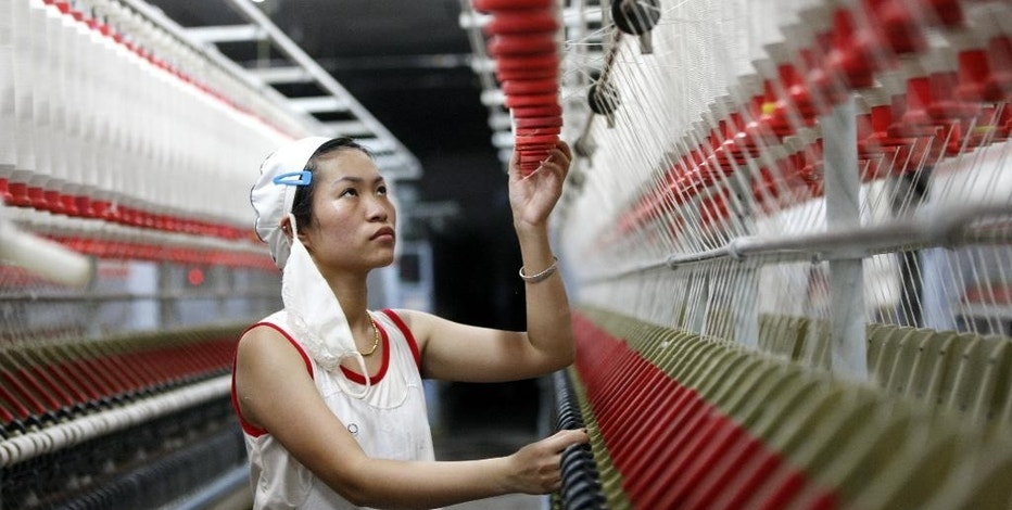 In this Friday, Aug. 28, 2015 photo, an employee works in a textile factory in Huaibei in central China's Anhui province. The world's second largest economy is decelerating, and the prospect of its slowing growth is rattling financial markets around the world. But China also is shifting _ from a dependence on exports and investment in factories, infrastructure and housing to a reliance on consumer spending from the country's emerging middle class. (Chinatopix Via AP, File) CHINA OUT