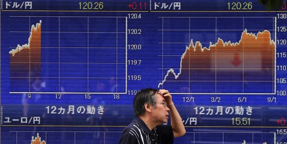 A man walks past an electronic stock board of a securities firm in Tokyo Wednesday, Sept. 9, 2015.  Japan's Nikkei 225 index gained more than 800 points during a morning trading. (AP Photo/Eugene Hoshiko)