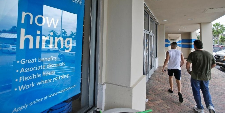 FILE - In this May 16, 2014 file photo, shoppers walk past a now hiring sign at a Ross store in North Miami Beach, Fla. The Labor Department releases weekly jobless claims on Thursday, Sept. 10, 2015. (AP Photo/Wilfredo Lee, File)