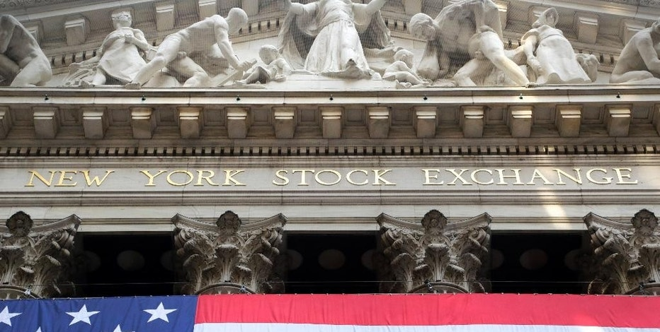 In this July 6, 2015 photo, an American flag is draped on the exterior of the New York Stock Exchange. Global stock markets fell Thursday, Sept. 10, 2015 after a strong U.S. job ads report boosted the case for the Federal Reserve to raise its interest rates next week for the first time in years.  (AP Photo/Mark Lennihan)