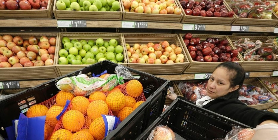 In this June 4, 2015 photo, a woman reaches for a bag of apples in the produce section of a Wal-Mart Supercenter store in Springdale, Ark. The Commerce Department releases wholesale trade inventories for July on Thursday, Sept. 10, 2015. (AP Photo/Danny Johnston, File)