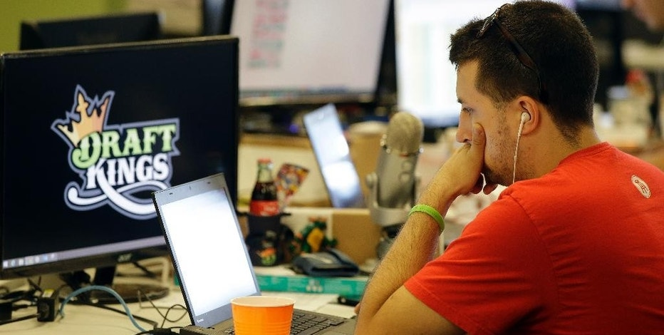 In this Wednesday, Sept. 9, 2015, photo, Devlin D'Zmura, a tending news manager at DraftKings, a daily fantasy sports company, works on his laptop at the company's offices in Boston. The daily fantasy sports industry is eyeing a breakout season as NFL games begin. And its two dominant companies, DraftKings and FanDuel, are touting lucrative opening week prizes to try to draw more customers as more competitors pop up. (AP Photo/Stephan Savoia)