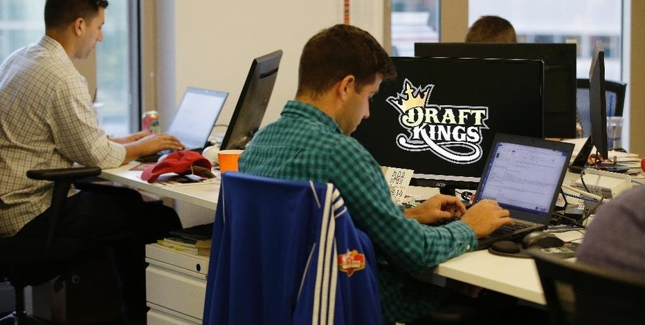 In this Wednesday, Sept. 9, 2015, photo, Bear Duker, a marketing manager for strategic partnerships at DraftKings, a daily fantasy sports company, works at his computer in Boston. The daily fantasy sports industry is eyeing a breakout season as NFL games begin. And its two dominant companies, DraftKings and FanDuel, are touting lucrative opening week prizes to try to draw more customers as more competitors pop up. (AP Photo/Stephan Savoia)