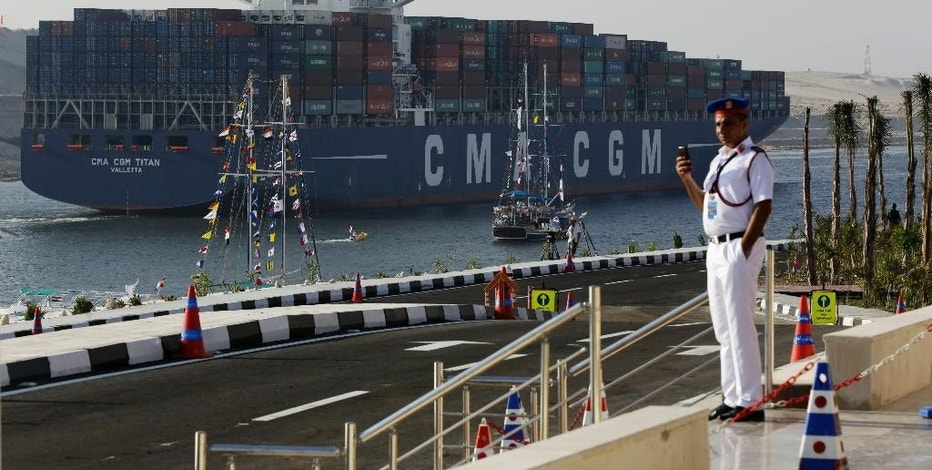 FILE - In this Thursday, Aug. 6, 2015 file photo, a cargo container ship crosses the new section of the Suez Canal after the opening ceremony in Ismailia, Egypt. In a few short years, if everything goes according to plan, Egypt will have new megaprojects, special investment zones and power plants fueled by the largest offshore gas field in the Mediterranean. But in the more immediate future, experts say the government needs to boost investment and bring in foreign capital to avoid a looming cash crunch. (AP Photo/Hassan Ammar, File)