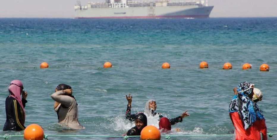 FILE - In this Sunday, Aug. 9, 2015 file photo, a ship crosses the Gulf of Suez towards the Red Sea as holiday-makers swim in Suez, 127 kilometers (79 miles) east of Cairo, Egypt. The centerpiece of Egyptian President Abdel-Fattah el-Sissi's efforts to jumpstart the economy was an extension of the Suez Canal unveiled in March and completed in August. But claims that annual revenues from the crucial waterway will be more than doubled to $13.2 billion by 2023 depend on a surge in global trade, which most experts think is unlikely. (AP Photo/Amr Nabil, File)