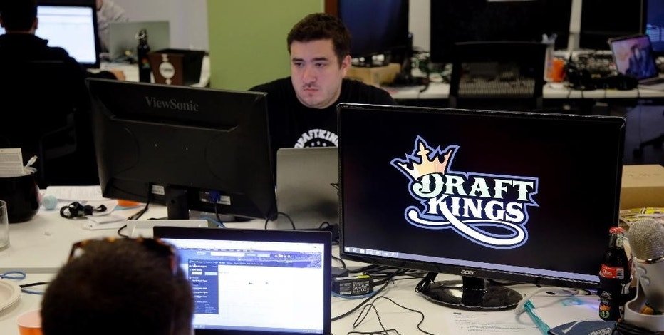 In this Wednesday, Sept. 9, 2015, photo, Len Don Diego, marketing manager for content at DraftKings, a daily fantasy sports company, works at his station at the company's offices in Boston. The daily fantasy sports industry is eyeing a breakout season as NFL games begin. And its two dominant companies, DraftKings and FanDuel, are touting lucrative opening week prizes to try to draw more customers as more competitors pop up. (AP Photo/Stephan Savoia)