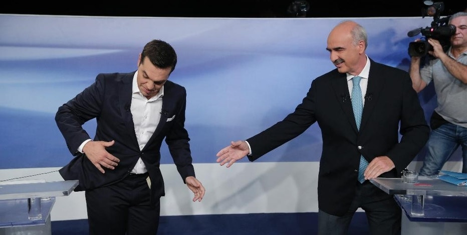 Former Greek Prime Minister Alexis Tsipras, left, and the leader of the left-wing Syriza party, is blocked by microphone wiring as he tries to approach main opposition conservative New Democracy head Vangelis Meimarakis, right, to shake hands prior to a live televised debate at the state-run ERT television in Athens, Monday, Sept. 14, 2015. Greece is holding a snap general election on Sept. 20, 2015. (AP Photo/Lefteris Pitarakis)