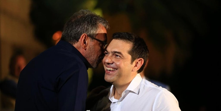 Former Greek Prime Minister Alexis Tsipras and the leader of the left-wing Syriza party, right, is welcomed by the Dionysis Tsaknis, left, President of state-run ERT television, as he arrives for a live televised debate with main opposition conservative New Democracy party head Vangelis Meimarakis, in Athens, Monday, Sept. 14, 2015.  Greece is holding a snap general election on Sept. 20, 2015. (AP Photo/Lefteris Pitarakis)