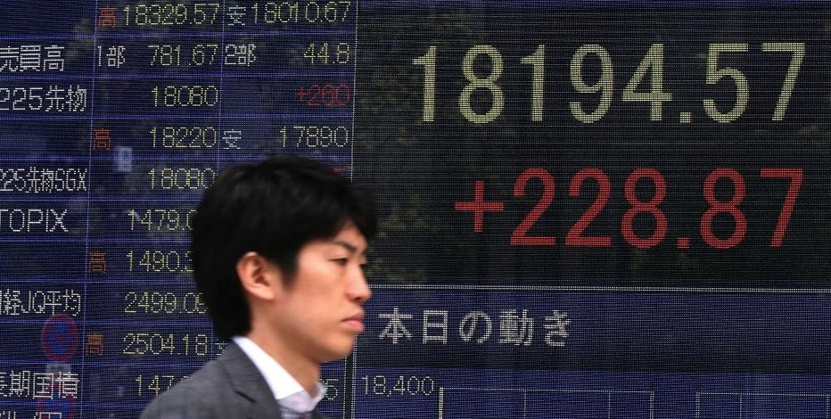 A man walks past an electronic stock board of a securities firm in Tokyo Tuesday, Sept. 15, 2015. Shares meandered in Asia on Tuesday as investors awaited a policy statement from the Bank of Japan as well as the U.S. Federal Reserve's decision later this week on whether to raise interest rates. (AP Photo/Eugene Hoshiko)