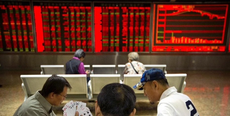 Chinese investors play cards at a stock brokerage house in Beijing, Wednesday, Sept. 16, 2015. Asian stocks rose Wednesday, tracking gains on Wall Street as investor optimism mounted ahead of a highly anticipated Federal Reserve policy meeting. (AP Photo/Mark Schiefelbein)