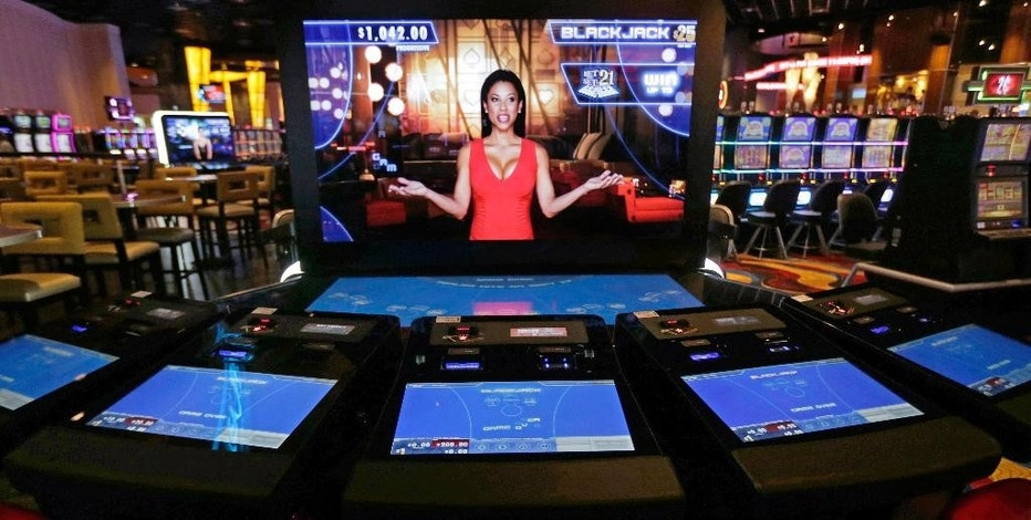 FILE - In this June 23, 2015, file photograph, an automated dealer asks for players to take a seat at a black jack video slot machine on the floor of the Plainridge Park Casino in Plainville, Mass. At the state's only casino, revenues were down in August, at about $15 million in gross gambling revenues, after posting about $18 million during July. (AP Photo/Charles Krupa, File)