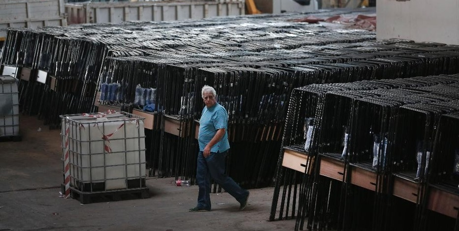 A municipal worker walks past voting booths to be loaded onto trucks at a depot in Athens, Thursday, Sept. 17, 2015, to be sent to polling stations for Sunday, Sept. 20 elections. Workers loaded 37 trucks with sacks of election materials, ballot boxes and voting booths. It is the third time this year Greeks will be voting, with the economy still in dire straits, a quarter of workers jobless, and capital controls limiting cash access to savings to 420 euros ($470) per week. (AP Photo/Lefteris Pitarakis)