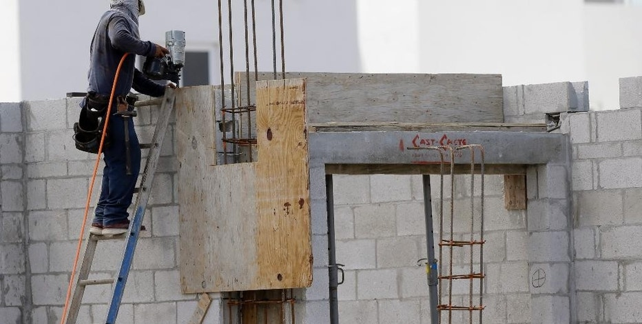 In this Monday, Aug. 17, 2015 photo, a builder works on the site of the Landmark community, a group of condos and townhouses built by Lennar Homes, in Doral, Fla. The Commerce Department reports on U.S. home construction in August on Thursday, Sept. 17, 2015. (AP Photo/Lynne Sladky)