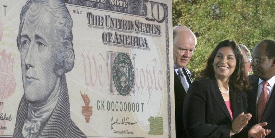 FILE - In this Sept. 28, 2005 file photo, John Snow, left, Secretary of the Treasury; Anna Escobedo Cabral, Treasurer of the United States, and Roger Ferguson, Jr., right, Vice Chairman for the Board Of Governors of the Federal Reserve System, attend the unveiling of the new $10 note on Ellis Island in New York harbor.  The announcement in June 2015 that the $10 dollar bill's redesign would replace Hamilton with a woman was welcomed but questioned.  Some have asked: Couldn't the more controversial, slave-owning President Andrew Jackson be removed from the $20 bill instead? (AP Photo/Bebeto Matthews)