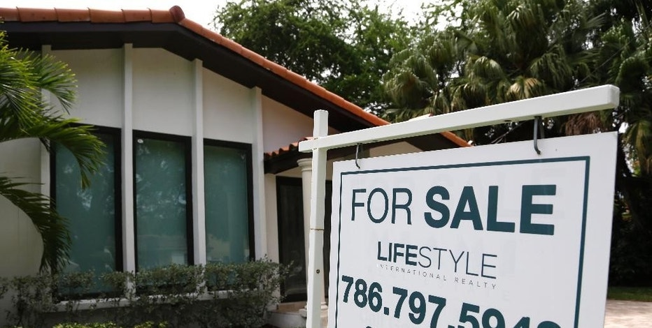 In this Saturday, Aug. 15, 2015 photo, a for sale sign is posted in front of a home in Miami. The National Association of Realtors reports on sales of existing homes in August on Monday, Sept. 21, 2015. (AP Photo/Lynne Sladky)