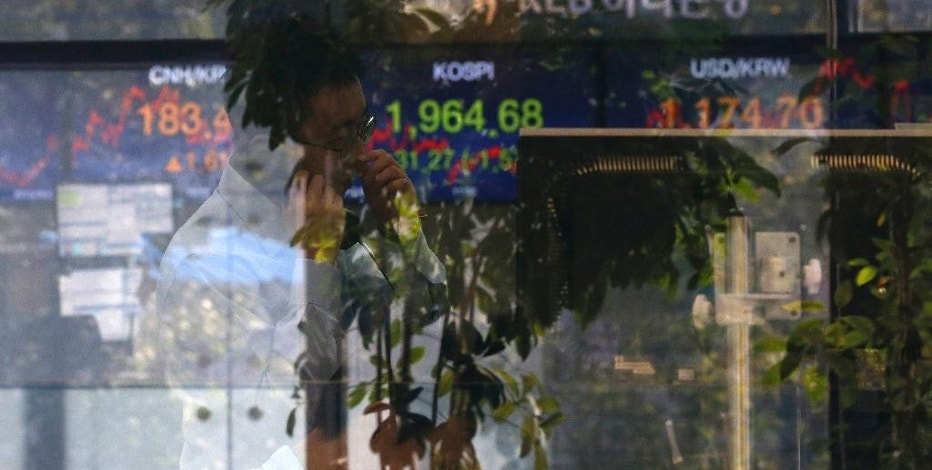 A currency trader talks on the phone near the screen showing the Korea Composite Stock Price Index (KOSPI) at the foreign exchange dealing room in Seoul, South Korea, Monday, Sept. 21, 2015. Asian stock markets were mostly lower Monday after concerns about global growth weighed on U.S. and European share prices. (AP Photo/Lee Jin-man)