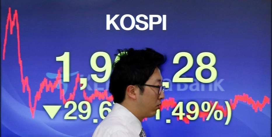 A currency trader walks near the screen showing the Korea Composite Stock Price Index (KOSPI) at the foreign exchange dealing room in Seoul, South Korea, Monday, Sept. 21, 2015. Asian stock markets were mostly lower Monday after concerns about global growth weighed on U.S. and European share prices. (AP Photo/Lee Jin-man)