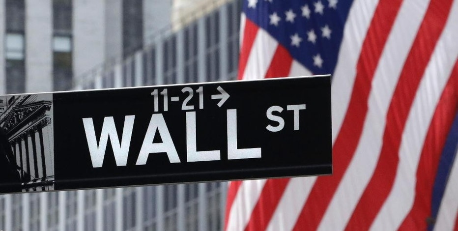 FILE - In this July 6, 2015, file photo, American flags fly at the New York Stock Exchange on Wall Street. Global stock markets were uneven Monday, Sept. 21, 2015, after the Fed's decision to delay a rate hike added to pessimism about global growth prospects. (AP Photo/Mark Lennihan, File)