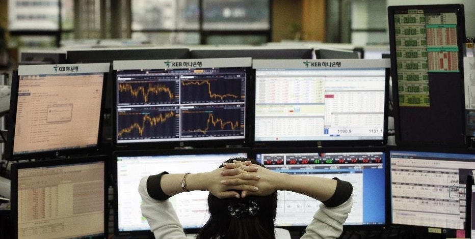 A currency trader watches monitors at the foreign exchange dealing room of the KEB Hana Bank headquarters in Seoul, South Korea, Wednesday, Sept. 23, 2015. Asian stock markets declined Wednesday as a global sell-off given impetus by the Volkswagen emissions scandal was exacerbated by weak Chinese factory data.(AP Photo/Ahn Young-joon)