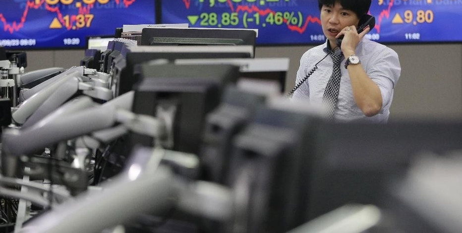 A currency trader speaks on the phone at the foreign exchange dealing room of the KEB Hana Bank headquarters in Seoul, South Korea, Wednesday, Sept. 23, 2015. Asian stock markets declined Wednesday as a global sell-off given impetus by the Volkswagen emissions scandal was exacerbated by weak Chinese factory data.(AP Photo/Ahn Young-joon)
