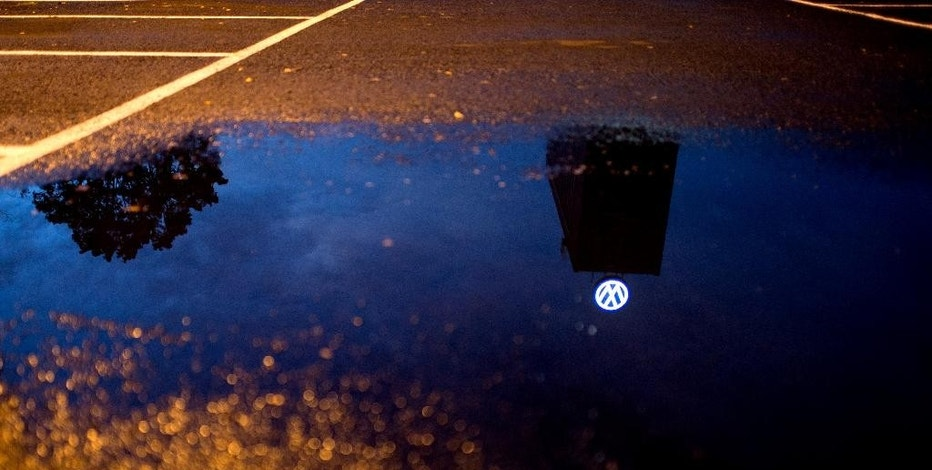 In this Sept. 22, 2015 photo a VW logo is reflected in a puddle at the Volkswagen headquarters in Wolfsburg, northern Germany. Volkswagen AG's smog-test scandal escalated Tuesday as the company acknowledged putting stealth software in millions of vehicles worldwide.  (Julian Stratenschulte/dpa via AP)