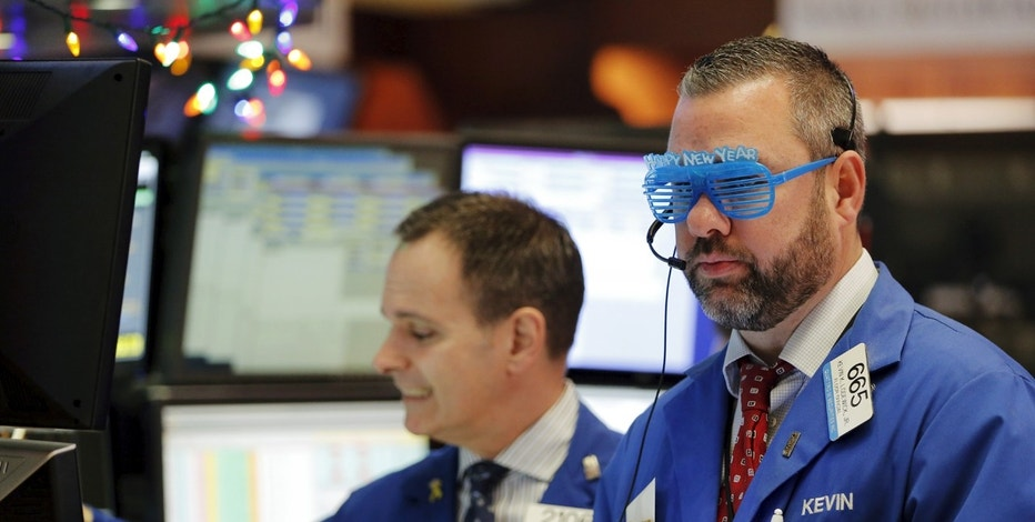 A trader wears plastic glasses to celebrate the last trading day of 2015 while working on the floor of the New York Stock Exchange