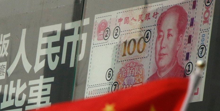 China's national flag is seen in front of a poster explaining the design of new 100 yuan banknote at a branch of a commercial bank at a business district in Beijing, China, January 21, 2016. REUTERS/Kim Kyung-Hoon - RTX23C1S