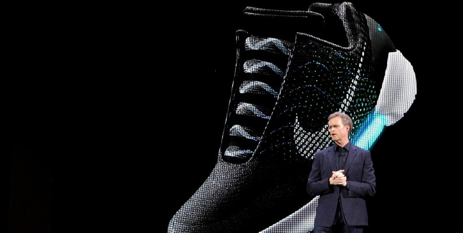 An image of the Nike HyperAdapt 1.0 is projected on a screen as Nike CEO Mark Parker speaks during a news conference, Wednesday, March 16, 2016, in New York.