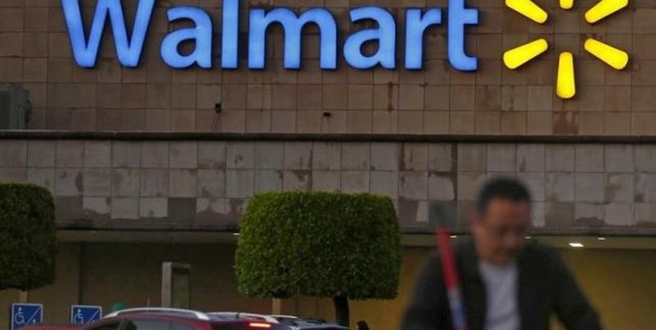 A shopper pushes a cart in front of a Wal-Mart store in Mexico City March 24, 2015.