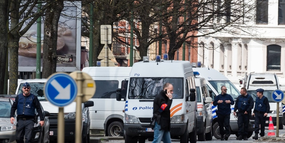 Police secure an area during a house search in the Etterbeek neighborhood in Brussels on Saturday April 9, 2016.