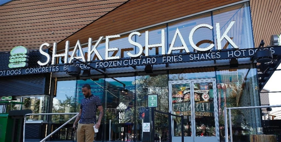 FILE - In this April 15, 2015 file photo, a man walks out of the Shake Shack in front of the New York-New York hotel and casino in Las Vegas. Shake Shack on Monday, Aug. 10, 2015 said that price hikes and the return of its crinkle-cut French fries helped lift sales 12.9 percent at established locations during the second quarter, and raised its outlook for the year. (AP Photo/John Locher, File)