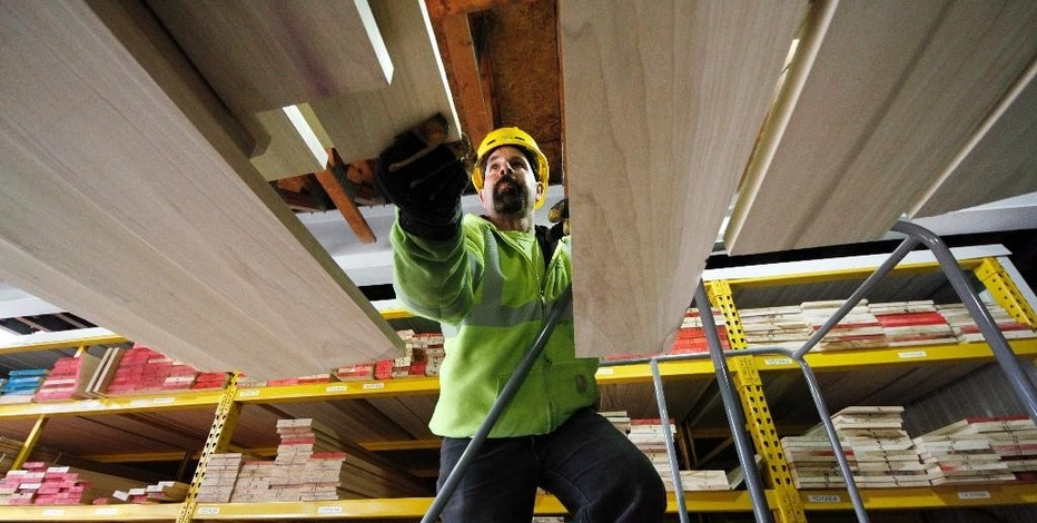 In this March 31, 2015, photo, Ed Fotta sorts hardwood at the Allegheny Millwork and Lumberyard in Pittsburgh. The Commerce Department releases business inventories for February on Tuesday, April 14, 2015.  (AP Photo/Gene J. Puskar)