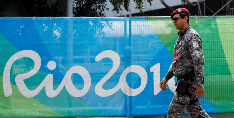 A soldier walks past a security fence outside the boxing arena as preparations continue for the 2016 Summer Olympics in Rio de Janeiro, Brazil, Wednesday, Aug. 3, 2016. (AP Photo/Vincent Thian)