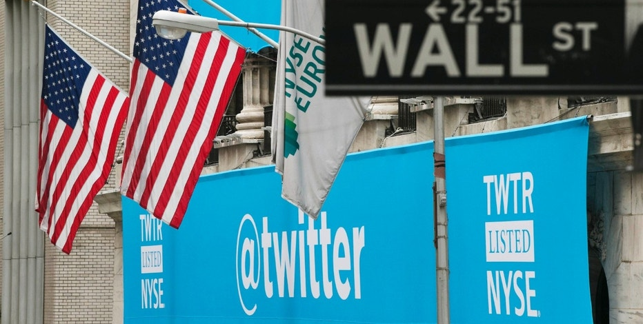 A sign displays the Twitter logo on the front of the New York Stock Exchange ahead of the company's IPO in New York, November 7, 2013.