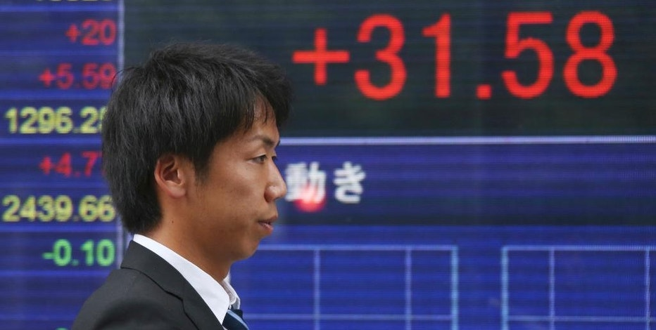 A man walks by an electronic stock board of a securities firm in Tokyo, Monday, Aug. 22, 2016. Asian stocks meandered on Monday as investors looked ahead to the Fed's meeting in Jackson Hole, Wyoming, for clues on timing for possible interest rate hikes. (AP Photo/Koji Sasahara)