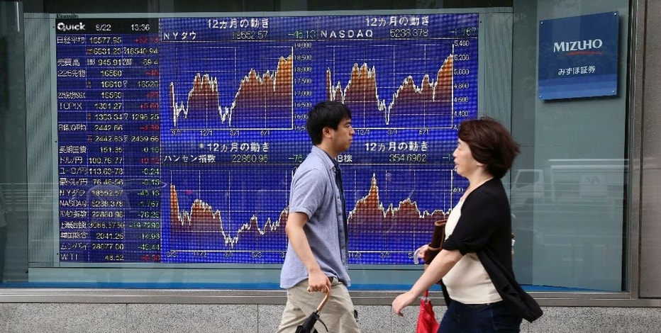 People walk by an electronic stock board of a securities firm in Tokyo, Monday, Aug. 22, 2016. Asian stocks meandered on Monday as investors looked ahead to the Fed's meeting in Jackson Hole, Wyoming, for clues on timing for possible interest rate hikes. (AP Photo/Koji Sasahara)