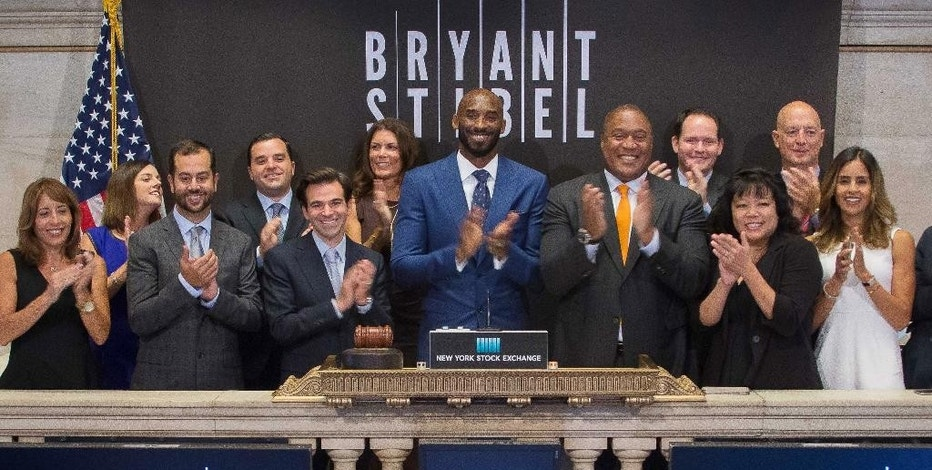 In this Monday, Aug. 22, 2016, photo provided by the New York Stock Exchange, retired NBA star Kobe Bryant, center, rings the opening bell with executives and guests of Bryant Stibel, at the NYSE in New York. Bryant has partnered with Jeff Stibel, an entrepreneur and investor, to form the $100 million venture-capital firm based in Los Angeles. (New York Stock Exchange via AP)
