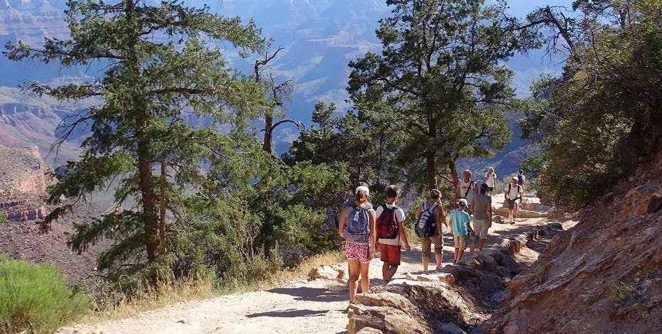 FILE - In this July 27, 2015, file photo, hikers cross paths along Bright Angel Trail heading into and out of the Grand Canyon at Grand Canyon National Park, Ariz. Zika fears are leading some to book away from the Caribbean and Florida. The American Southwest, New England and Bermuda are providing a virus-free alternative, but destinations are hesitant to market themselves as such. (AP Photo/Ross D. Franklin, File)