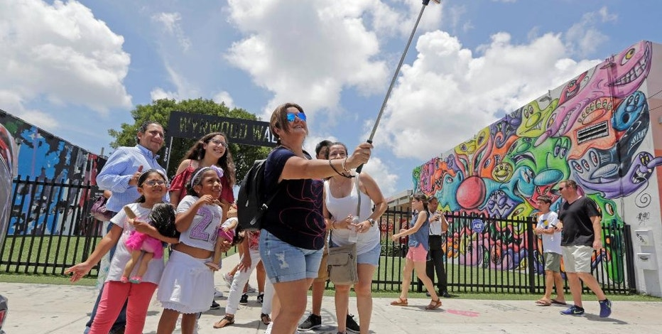 FILE - In this Friday, Aug. 5, 2016, file photo, a family from Peru takes a selfie in front of the Wynwood Walls, in the Wynwood area of Miami. The recent announcement that more than a dozen people have been infected with Zika by mosquitoes in the area has scared away some, but many others are still coming. The American Southwest, New England and Bermuda are providing a virus-free alternative, but destinations are hesitant to market themselves as such. (AP Photo/Alan Diaz, File)
