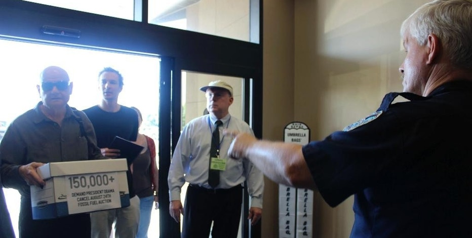 A Jefferson Parish sheriff's deputy, right,  tells protesters John Clark, carrying a box with a copy of a petition against federal oil lease sales, and Blake Kopcho, second from left, that they cannot enter the building where the leasing agency has offices, Tuesday, Aug. 23, 2016 in Harahan, La. The protest was Tuesday, a day before the Bureau of Ocean Energy Management has scheduled a lease sale for Gulf of Mexico water bottom off of Texas. Legal observer Bill Qugley, wearing hat, said Clark and Kopcho were among four demonstrators later arrested on a charge of trespassing. (AP Photo/Janet McConnaughey)
