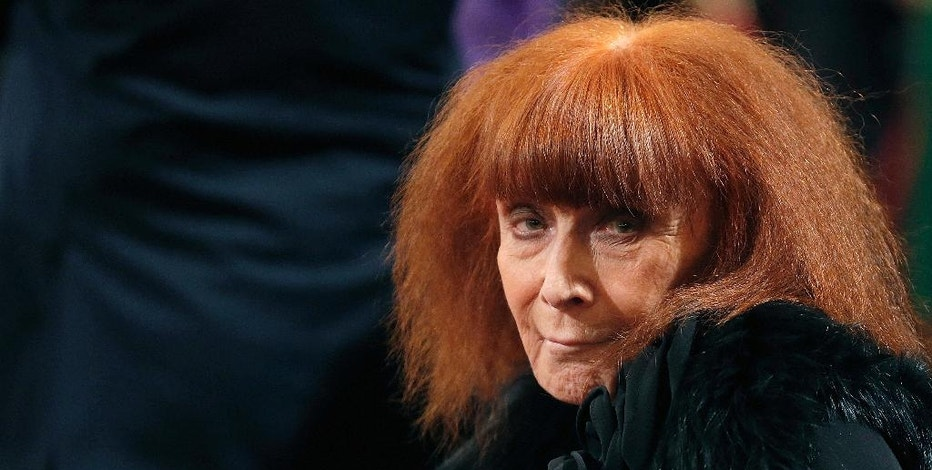 FILE - In this Nov. 26, 2013 file photo, French fashion designer Sonia Rykiel attends a ceremony in Paris. Rykiel, whose relaxed striped sweaters helped liberate women from their stuffy suits and who went on to run a global fashion empire, has died at 86, according to the French president's office.(Christian Hartmann, Pool via AP, File)