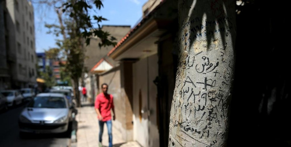 This Tuesday, Aug. 2, 2016 photo, shows handwritten advertisements for human kidneys for sale that includes the sellers' phone number and blood type, on a tree in downtown Tehran, Iran. A unique system allows those in need of a transplant to buy a kidney. The program, which has seen Iran's waitlist for kidneys effectively drop to zero, has been championed by some Western doctors as a way to cut time for lifesaving transplants. However, some ethicists worry about the system taking advantage of the poor worldwide to black-market organ sales. (AP Photo/Ebrahim Noroozi)